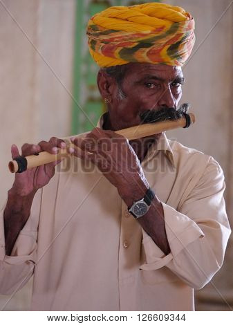 RAJASTHAN, INDIA: MARCH 2016 Close up of a Rajasthani man with the colourful turban and large moustache, typical of that northwestern state of India, playing a traditional wooden flute.