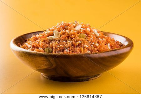 tasty gajar halwa or gajar ka halwa made up or fresh carrot, sugar and milk. decorated with almond or badam, cashewnuts and pistachios, favourite north indian dessert usually served in indian weddings poster