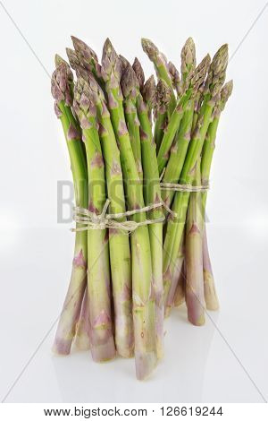 Two Bunches Of Asparagus Tied With Raffia Cord, Isolated On White Background.