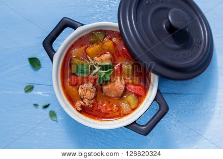 Goulash In A Black Cocotte With Marjoram On Blue Wood