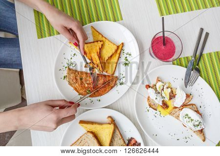 Closeup on a young girl's hands as she is having american breakfast. Pancace, eggs, bacon with toast.
