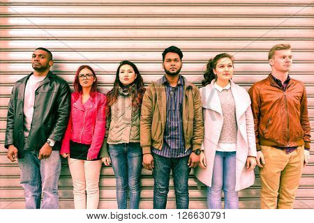 Multiracial serious people lineup as mugshot is standing next to metal rolling shutter - Unemployed multi ethnic friends line up outdoor - Concept of discrimination and youth concern for the future poster