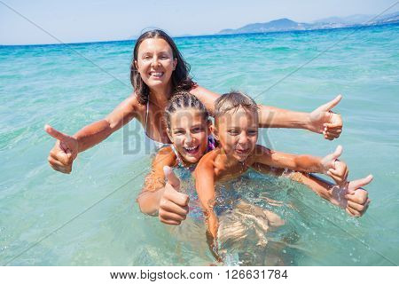 Photo of happy family in clear water looking at camera during summer vacation