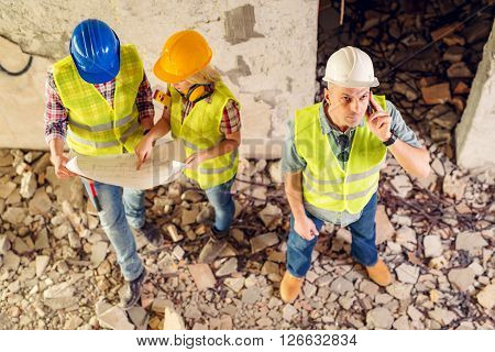 Construction architects using phone in building damaged in the disaster. His colleagues review plan.