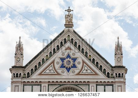 Marble facade of Santa Croce Church in Florence Italy. The ornate facade is a Florentine landmark and constructed of white green and pink marble.