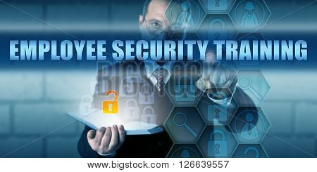 HR director is pressing EMPLOYEE SECURITY TRAINING on a virtual touch screen interface. Business challenge metaphor and information technology concept for computer security education for staff.