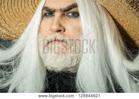 Bearded senior man in long white wig and straw round hat on wooden background