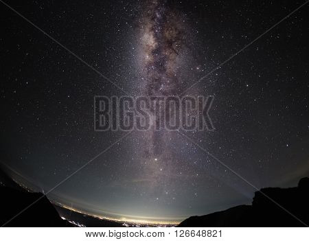 Part of a night sky with stars and Milky Way on equatorial latitude with green tropical trees below