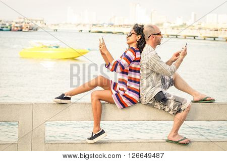 Travelers couple in disinterest moment with mobile phones at Pattaya beach - Apathy and addiction concept with bored people using smartphones - Soft desaturated filter with slight tilted horizon