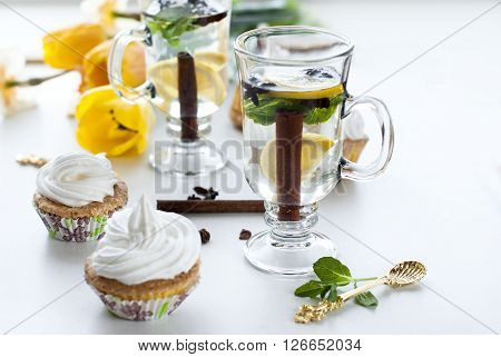 tea with lemon cinnamon and mint in high glasses and muffins with cream on a white background selective focus