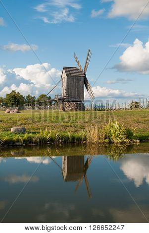 Old wooden windmill with reflection in the water, Angla, Island of Saaremaa, Estonia.