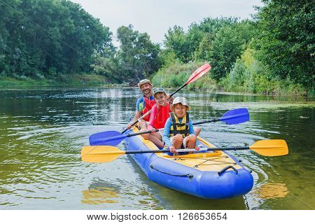 Active happy family. Boy with his sister and father having fun together enjoying adventurous experience kayaking on the river on a sunny day during summer vacation