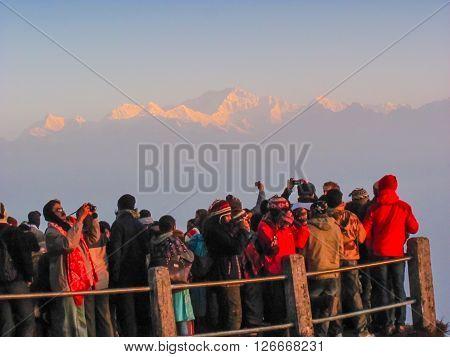 Darjeeling, India - 27th Feb 2012: Tourists on walkway in Darjeeling looking at the Himalayan range at dawn