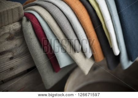Layers Of Folded Color Linen Hanging On Crate