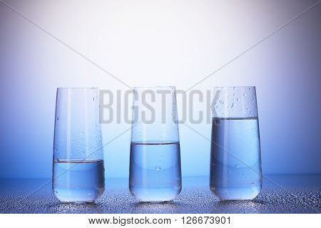 One-third, Half-filled And Two-thirds Full Drinking Glasses
