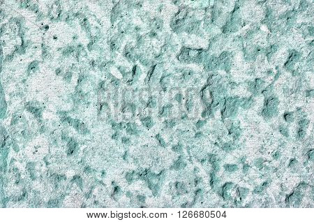 Detailed surface of stone light green wall with fine grooves - textured background.