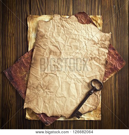 Old key and paper on wood background