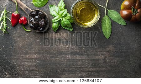 Food background with vegetables, herbs and condiment. Greek black olives, fresh basil, sage, rosemary, tomato, peppers, oil on dark rustic wooden background.  Top view, copy space