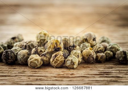 Dry green peppercorn on wooden background macro