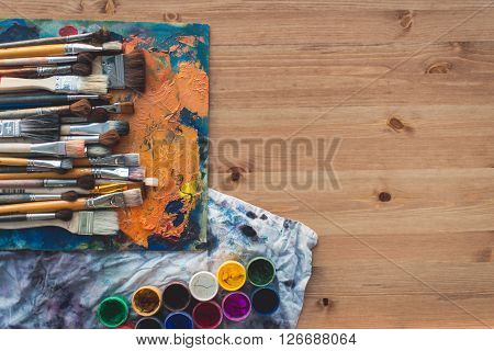 Different size paintbrush collection on an old palette with oil paint colors blend and a gouache set, top view picture