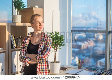 Young female artist standing at art studio, holding arms folded across, her workplace, smiling, looking aside. Designer with artistic tools on work-table ready to work in office