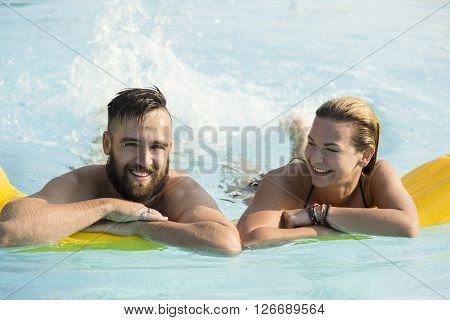 Couple in love floating on a pool matress and having fun on their summer vacation