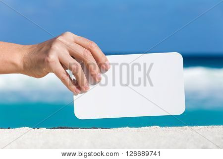 Blank White Board In Female Hand On Sand Against Turquoise Caribbean Sea Water