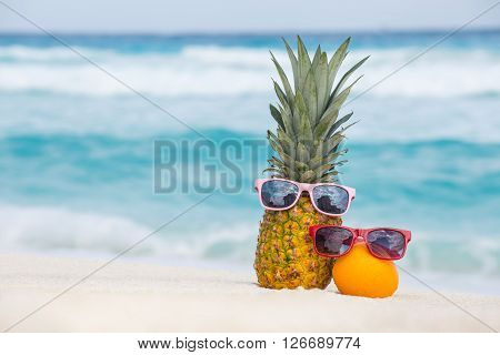 Pineapple And Orange Fruits In Sunglasses On Sand Against Turquoise Caribbean Sea Water