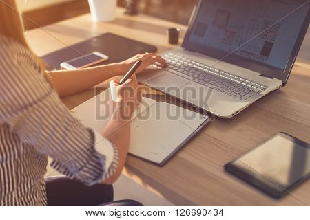 Female designer using laptop, sketching at blank notepad. Woman hand writing in notebook on wooden desk