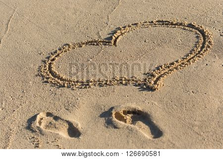 Shape Of Heart And Footprints On Sand