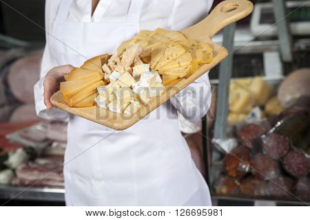 Saleswoman Holding Cutting Board With Assorted Cheese