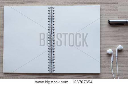 black pen earplugs and open notebook on wooden.