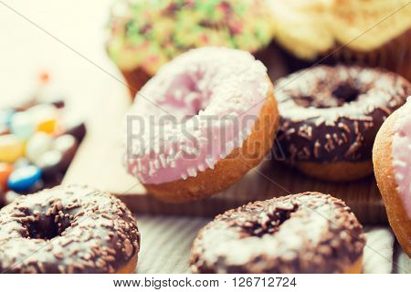 food, junk-food and eating concept - close up of glazed donuts on table