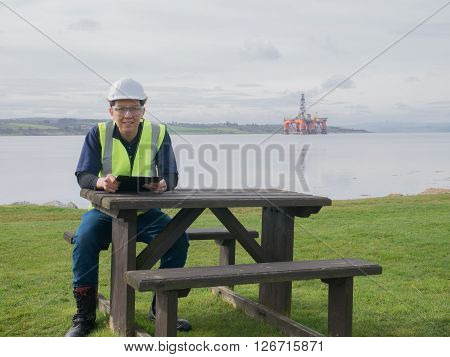 An asian engineer sitting on the desk in front of semi submersible oil rig