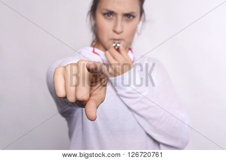 Portrait of young beautiful woman with whistle and pointing camera. Isolated white background.