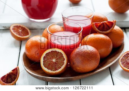 Fresh delicious juice with red oranges on wooden plate selective focus