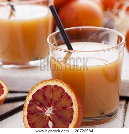 Close up of delicious juice with red oranges on white wooden background selective focus square image