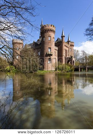 Bedburg-Hau, Germany - April 17, 2016: South-western view of Castle Moyland in the district of Kleve, one of the most important neo-Gothic buildings in North Rhine-Westphalia