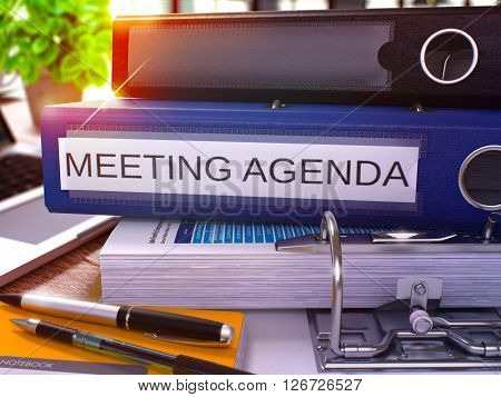 Meeting Agenda - Blue Ring Binder on Office Desktop with Office Supplies and Modern Laptop. Meeting Agenda Business Concept on Blurred Background. Meeting Agenda - Toned Illustration. 3D Render.