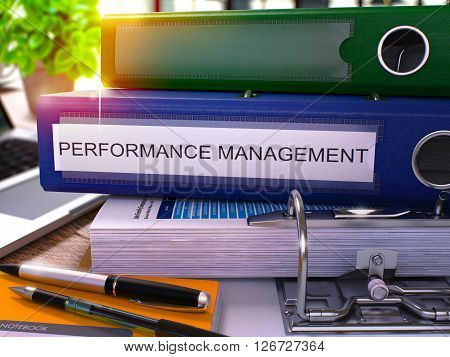 Blue Office Folder with Inscription Performance Management on Office Desktop with Office Supplies and Modern Laptop. Performance Management Business Concept on Blurred Background. 3D Render.