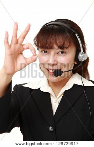 studio shot of businesswoman showing perfect sign