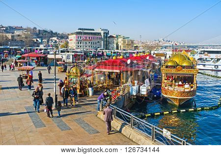 ISTANBUL TURKEY - JANUARY 21 2015: The Eminonu promenade attracts the tourists with floating restaurants adjacent Egyptian Bazaar and views on the Golden Horn Bay and opposite banks on January 21 in Istanbul.