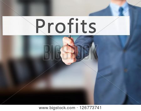 Profits - Businessman Hand Holding Sign