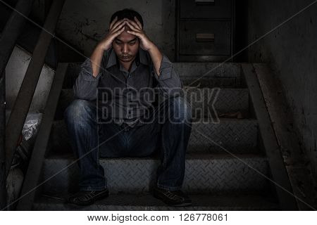 depressed businessman sitting on the stairs in scary abandoned building.