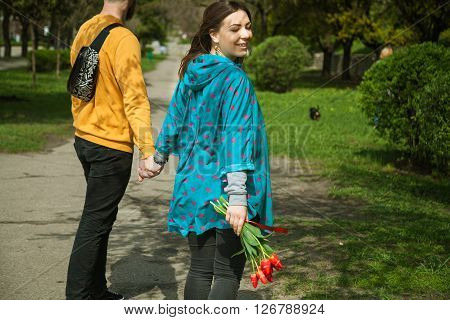 happy young woman pulling boyfriend's hand smiling inviting to join - follow me - hipsters hand in hand best friends cheerful girl dating guy outdoors