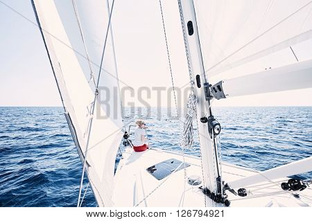 Young blonde woman wearing sunglasses and red shorts, sitting on deck under sails on yacht bow and enjoying wonderful view to peaceful sea during summer sailing holidays - yacht charter concept