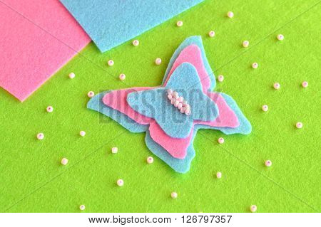 Felt butterfly on a green background, beads, blue and pink sheets