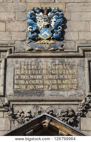 A plaque on the exterior of Canongate Kirk in Edinburgh detailing the history of the building.