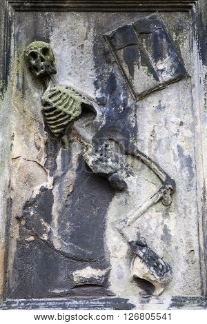 EDINBURGH SCOTLAND - MARCH 11TH 2016: A dancing skeleton carrying a scythe on the headstone of the grave of James Borthwick of Stow in Greyfriars Cemetery in Edinburgh on 11th March 2016.