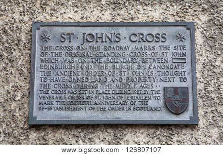 A wall plaque on Canongate detailing the former site of the original St. Johns Cross along the Royal Mile in Edinburgh Scotland.
